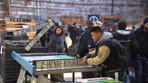 Plusieurs personnes manipulent de vieilles enseignes pour les stations de métro Henri-Bourassa et Lionel-Groulx sur des tables disposées dans un garage de la STM.
