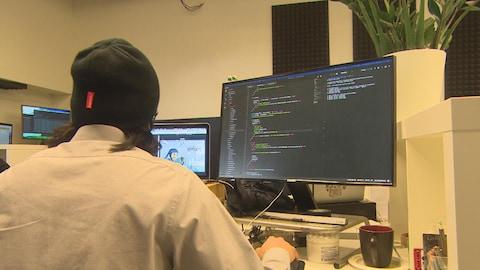 Un homme coiffé d'une tuque est assis à un ordinateur à l'écran duquel est affiché du codage.