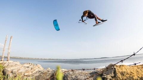 Lucas Arsenault sur une petite planche de surf saute dans les airs emporté par un grand cerf-volant, près d'une plage.