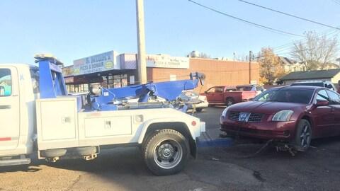 Une remorqueuse déplace la voiture rouge du suspect arrêté.