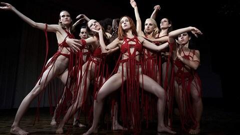 Des femmes vêtues de morceaux qui ressemblent à des cordes rouges sont regroupées pour une pose extraite d'un spectacle de danse.