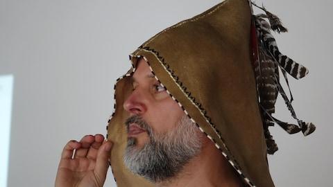 Homme avec un chapeau sur la tête, qui a des plumes.