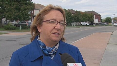 Sylvie Goneau en entrevue à Radio-Canada à l'extérieur, devant une rue