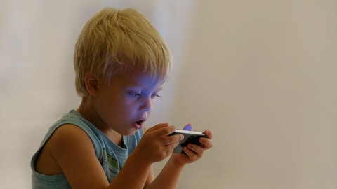 Little cute boy enthusiastically playing video games on portable device. For fun and joy. Concept: cell phone addiction