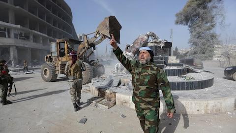 Un soldat en habit militaire devant le promontoire d'une statue détruite, par un engin de chantier, à gauche de l'image.