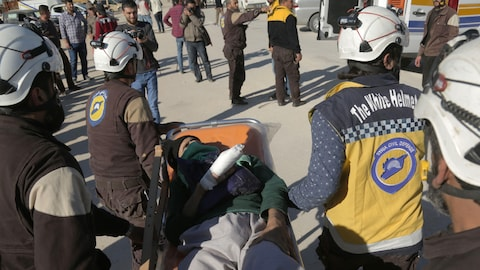 Des membres des Casques blancs (aussi appelés Défense civile syrienne) transportent un homme couché sur une civière, la main droite enroulée dans un bandage.