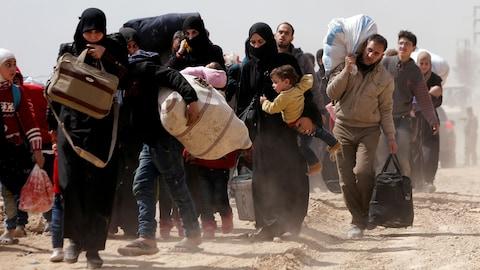 Des Syriens fuient leur village dans la Ghouta orientale.