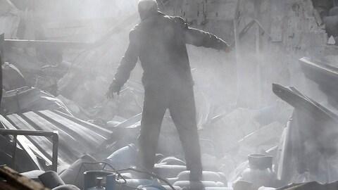 Un homme se tient sur les ruines d'une maison détruite dans une région tenue par les rebelles syriens, près de la capitale, Damas.