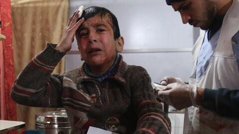 Un garçon pleure pendant qu'il tient un pansement sur sa tête. Un membre du personnel médical est à ses côtés.