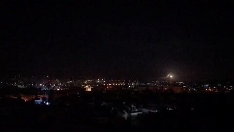 Une photo tirée d'une vidéo montre un point lumineux au loin dans la nuit sur une ville syrienne.