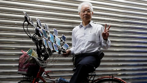 "Taiwanese Chen San-yuan, 70, known as ""Pokemon grandpa"", poses with his bicycle as he plays the mobile game ""Pokemon Go"" by Nintendo, near his home with 15 mobile phones, in New Taipei City, Taiwan November 12, 2018. Picture taken November 12, 2018. REUTERS/Tyrone Siu - RC1A78B353B0"