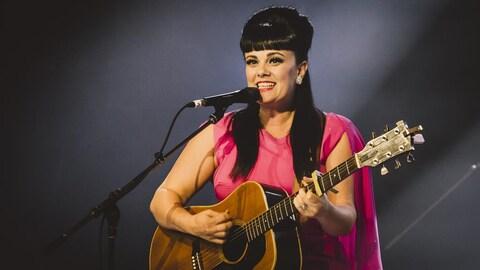 La jeune femme joue de la guitare et chante.