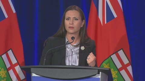 Tanya Granic Allen sur scène, devant des drapeaux de l'Ontario.