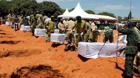 Des agents de sécurité s'apprêtent à enterrer certaines des victimes du naufrage de jeudi.
