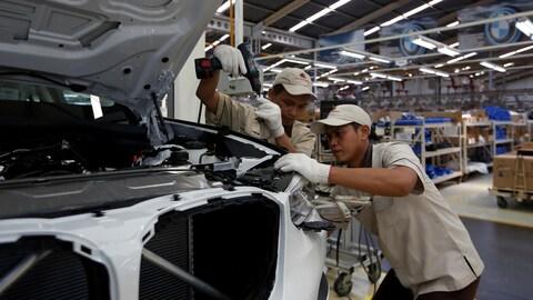 Deux ouvriers travaillent sur une voiture dans une chaîne d'assemblage
