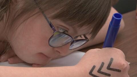 Une jeune fille dessine avec sur la main le tatouage de trois petits chevrons