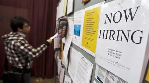 Une personne devant un tableau d'annonces d'emploi.