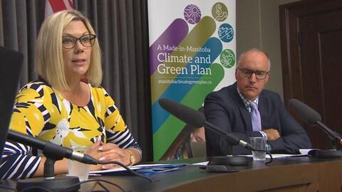 Une femme et une homme portant des lunettes sont assis en face de microphones et devant une bannière colorée.