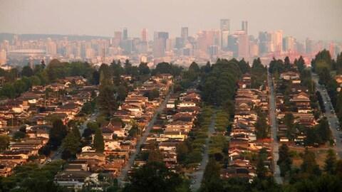Photo très large sur le centre-ville de Vancouver avec des rangées de maisons en avant-plan.