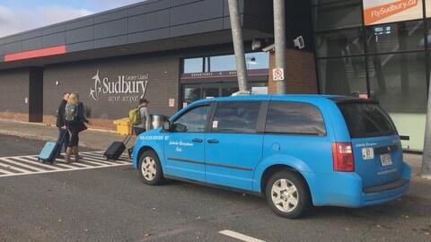 Un taxi bleu est stationné devant l'entrée de l'aéroport de Sudbury.