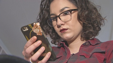 Une jeune femme portant des lunettes et ayant les cheveux frisés, regarde l'écran de son téléphone cellulaire
