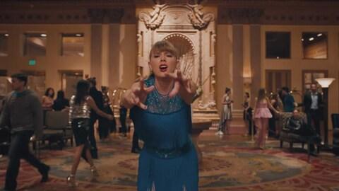 Vêtue d'une robe bleue, Taylor Swift tend les bras dans un salon d'hôtel, dans le clip  Delicate .