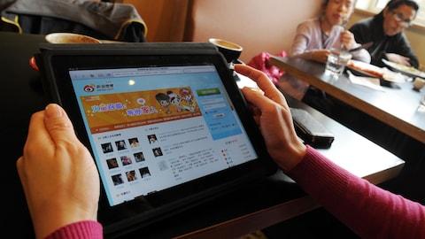 Une femme consulte le réseau social Weibo dans un café chinois.