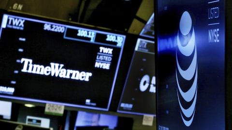 Les logos de ATT et Time Warner sont affichés sur des écrans à la Bourse de New York.