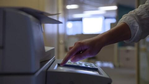 Une dame appuie sur un bouton d'un télécopieur.