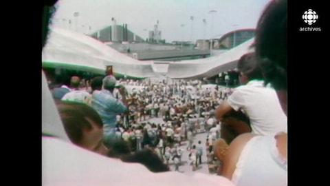 Des centaines de personnes se tiennent dans la cour du stade olympique à Montréal.