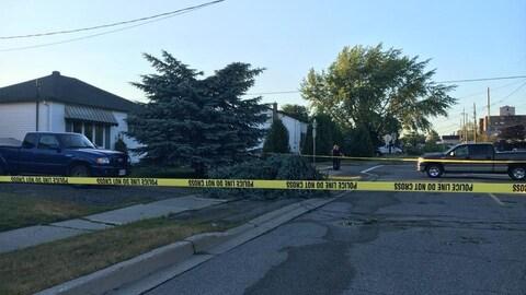 Une zone protégée par un cordon policier et un arbre déraciné sur un trottoir.