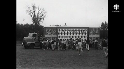 Le camion-remorque transportant le théâtre La Roulotte est  entouré d'enfants.