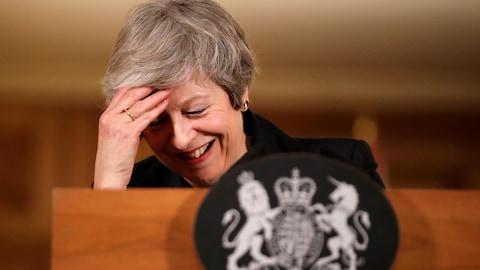 Theresa May rit et touche son front avec sa main pendant une conférence de presse.