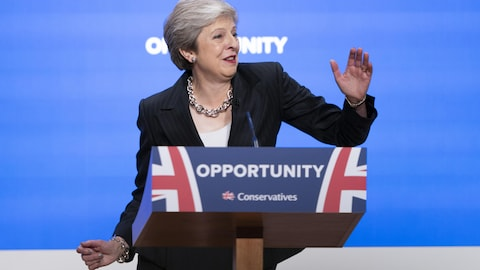 Theresa May balance les bras en souriant.