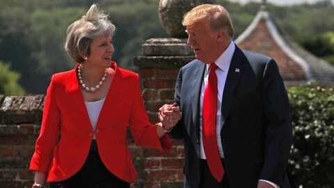 Theresa May et Donald Trump s'empoignent la main.