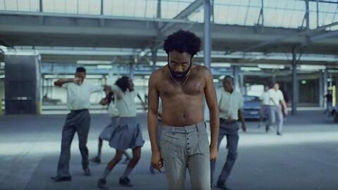 Torse nu, Childish Gambino regarde la caméra de manière menaçante, alors que des jeunes dansent derrière lui dans un stationnement, dans une scène du clip «This is America».