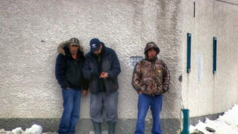 Trois personnes appuyées contre un mur du Regal Beagle Tavern, un bar de Thompson.