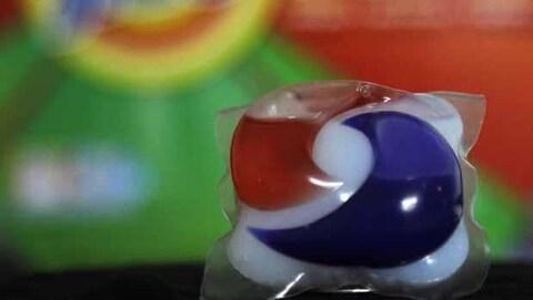 Une capsule de détersif bleue, rouge et blanche.
