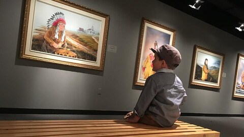 Un jeune garçon sur un banc regarde les toiles de chefs autochtones