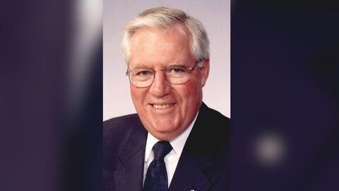 Tom Molloy, un homme aux cheveux blancs et portant de lunettes.