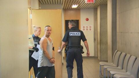 Un homme avec des menottes aux poignets est accompagné de deux policiers.