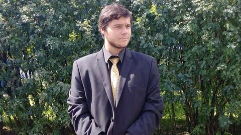 Un jeune homme porte un veston et une cravate jaune.  Il pose devant la caméra.