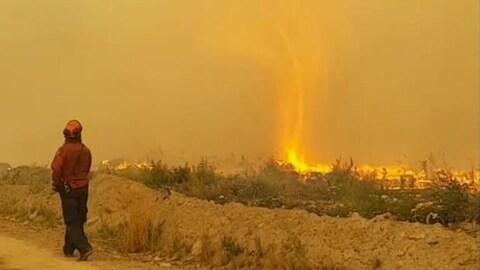 Une personne marche dans la fumée sur un chemin de terre. Une colonne de feu s'élève au loin.