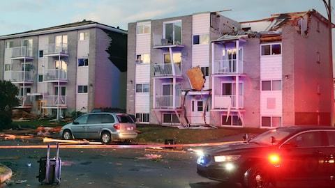 Le toit d'un immeuble de logements est arraché et des débris jonchent la rue.