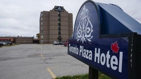 Photo de l'enseigne bleue d'un hôtel, l'édifice en briques brunes est en arrière-plan.