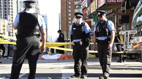 Trois policiers près de corps sur le trottoir.