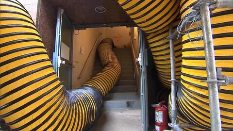 Des tuyaux d'aération serpentent dans une cage d'escalier.