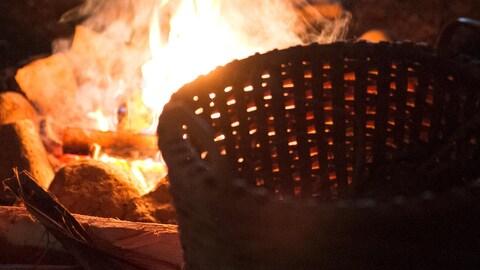Gros plan d'un panier de paille près d'un feu.