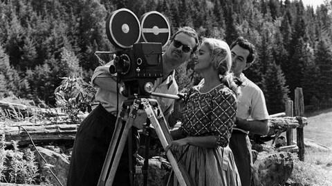 À l'extérieur, près d'une forêt, le réalisateur Fernand Quirion, Donalda Laloge-Poudrier (Andrée Champagne) et le caméraman André Fleury regarde à travers le viseur d'une caméra.
