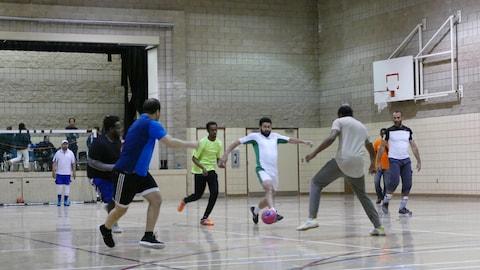 Un petit groupe d'hommes disputant une partie de soccer dans un gymnase d'école.
